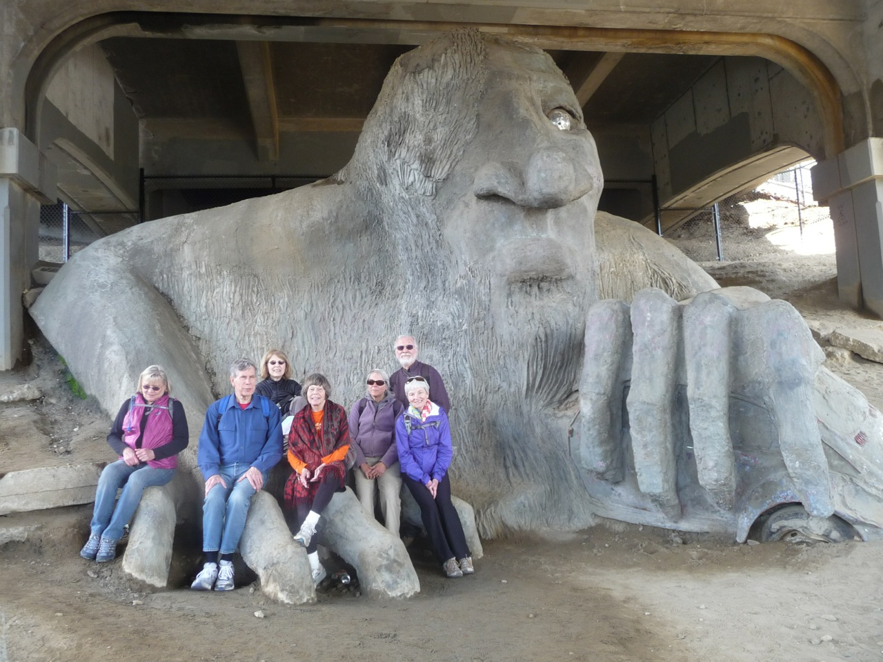 Frances, Al, Judy, Kathy, Kathryn, Dan, Annie sit on the Fremont Troll.